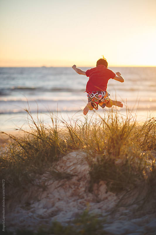 Boy leaping off a dune at the beach by Angela Lumsden for Stocksy United