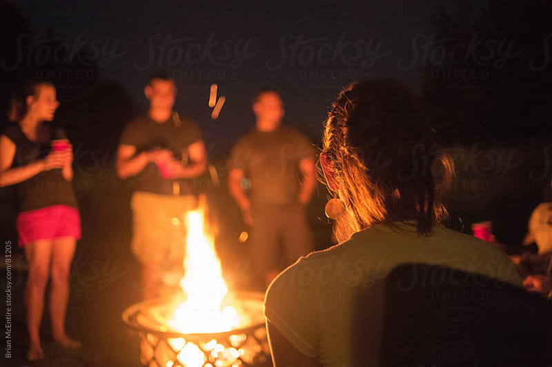 Mid 20s Aged Friends Gathered Around a Campfire During House Party by Brian McEntire for Stocksy United
