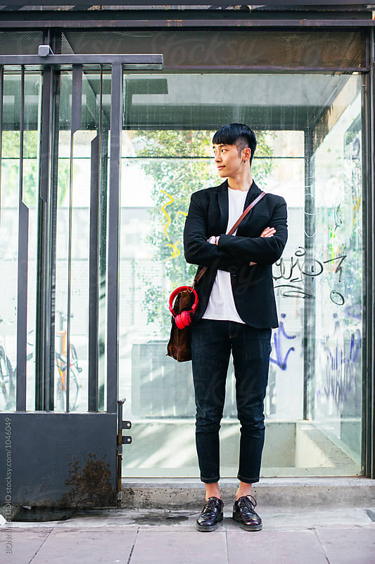 Stylish asian businessman waiting on the street. by BONNINSTUDIO for Stocksy United