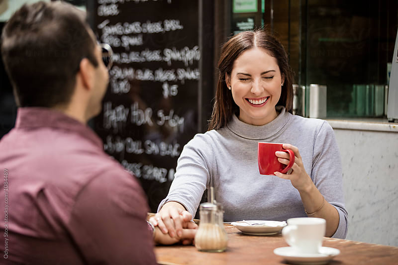 Woman Drinking Coffee at Outdoor Cafe Laughing by Odyssey Stock for Stocksy United