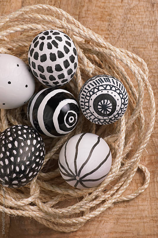 Easter eggs with different drawings on a rope. Wood background. by BONNINSTUDIO for Stocksy United