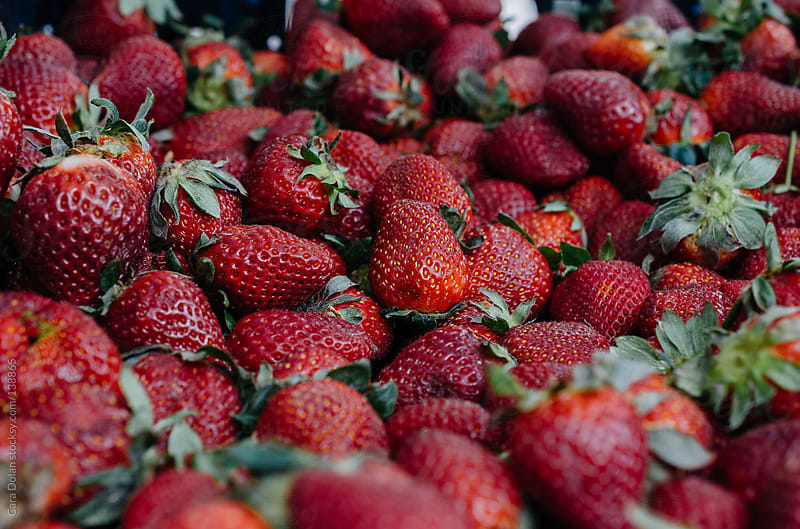 Fresh red strawberries for sale at a farmer's market by Cara Dolan for Stocksy United