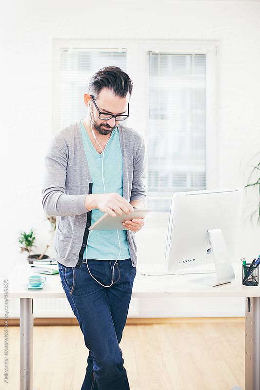 Young casual dressed man working on tablet at the office by Aleksandar Novoselski for Stocksy United