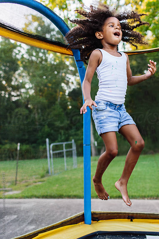 A young girl jumping on a trampoline as her hair flies in the air by Kristen Curette Hines for Stocksy United