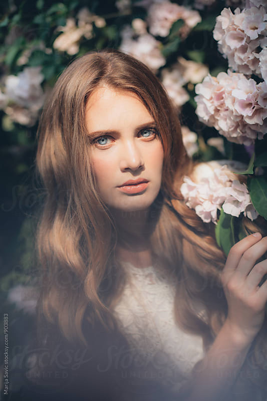 Beautiful Blue-eyed Woman in a Tropic Garden  by Marija Savic for Stocksy United