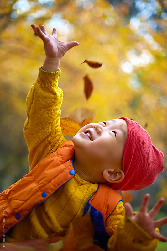 happy little boy playing with leaf in the autumn woods by Bo Bo for Stocksy United