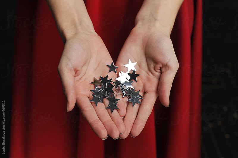 Girl holding on silver stars by Lyuba Burakova for Stocksy United