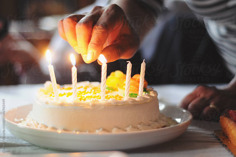 Woman lighting candles on a birthday cake by Chelsea Victoria for Stocksy United