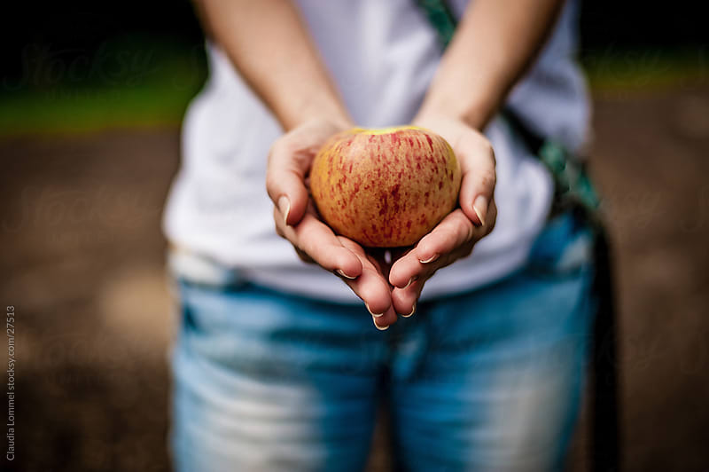 Woman Presenting an Apple by Claudia Lommel for Stocksy United