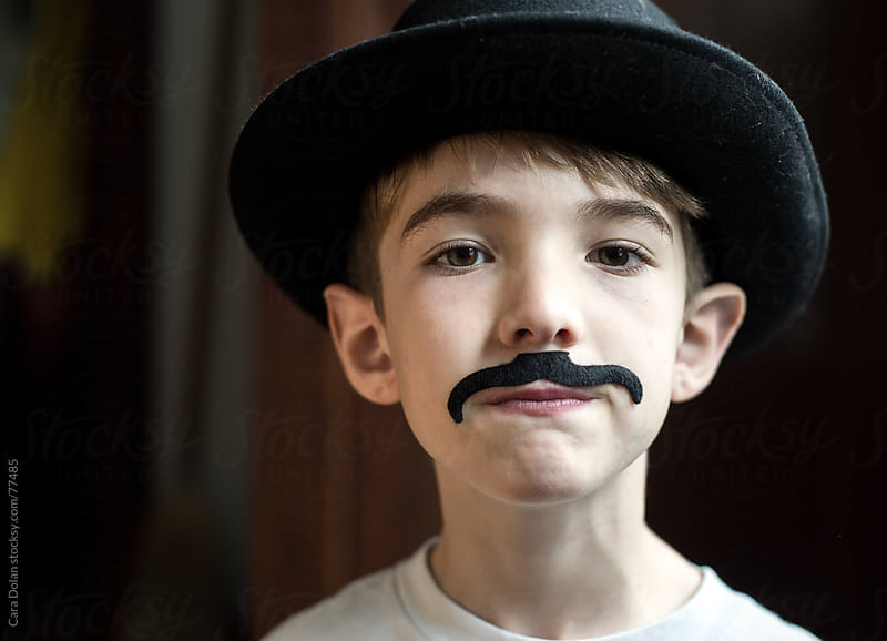Boy plays dress up with old hat and fake mustache by Cara Dolan for Stocksy United