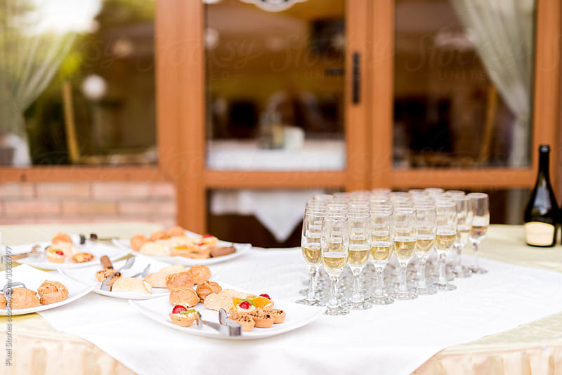 Wedding reception with finger food and champagne by Pixel Stories for Stocksy United