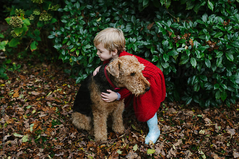 Girl hugging an Airedale dog in a garden by Julia Forsman for Stocksy United