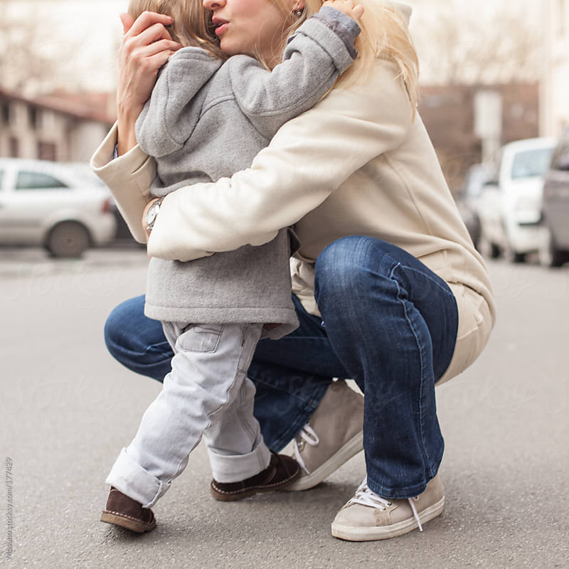 Anonymous Mother and Child Hugging on the Street by Mosuno for Stocksy United