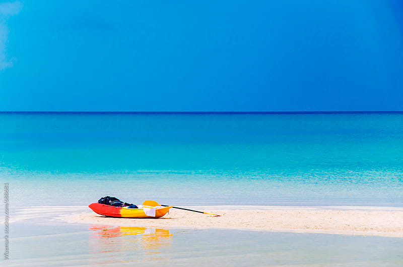 Sea kayak parked on a stretch of a perfect, postcard, white sand beach by Srdjan Kirtic for Stocksy United