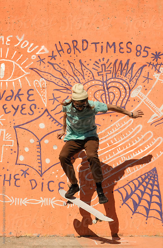 Hip young male in urban outfit doing tricks on skateboard in front of graffiti. by Marko Milanovic for Stocksy United