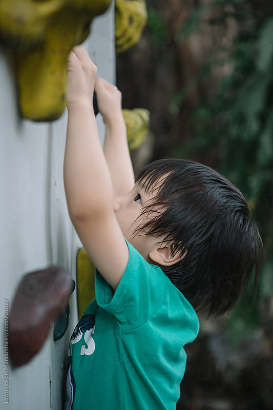 A very young kid practicing wall climbing works hard to reach the farthest end of the wall by Lawrence del Mundo for Stocksy United