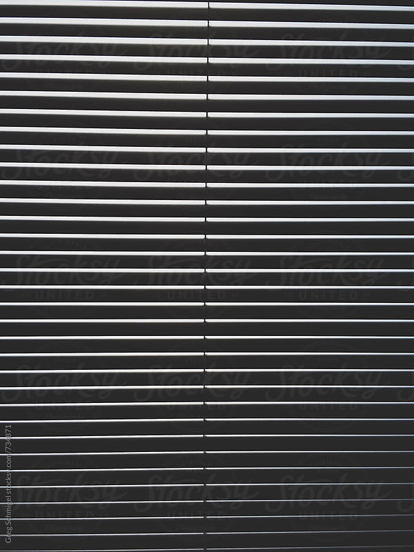 Abstract detail, pattern and texture of light and shadow shining through window blinds by Greg Schmigel for Stocksy United