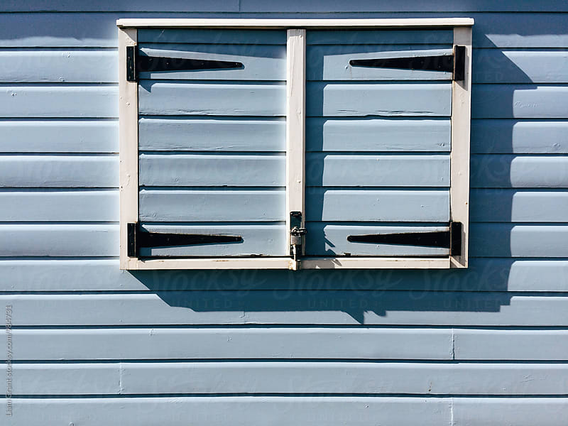 Window shutters on a blue wooden panelled beach hut. Norfolk, UK. by Liam Grant for Stocksy United