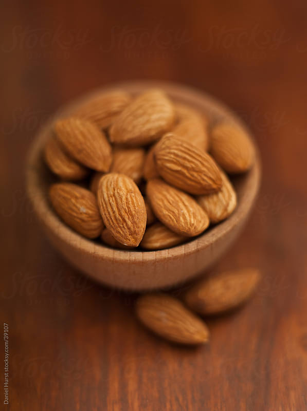Almonds in small bowl by Daniel Hurst for Stocksy United