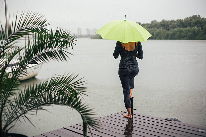 Woman by the river on a rainy day by Jovo Jovanovic for Stocksy United