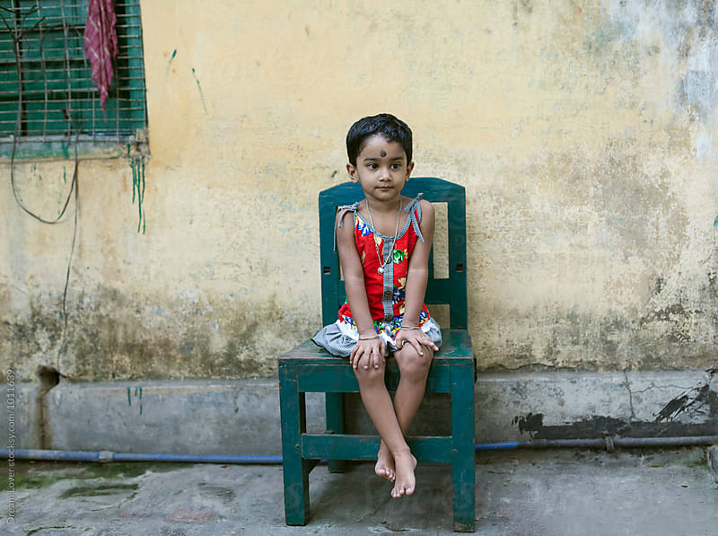 A little girl sit on a chair by PARTHA PAL for Stocksy United