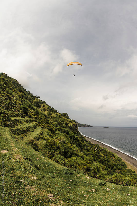 Man paragliding along coastline over ocean by Søren Egeberg Photography for Stocksy United