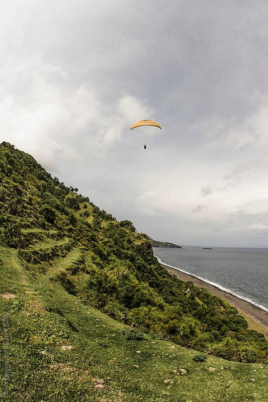 Man paragliding along coastline over ocean by Soren Egeberg for Stocksy United