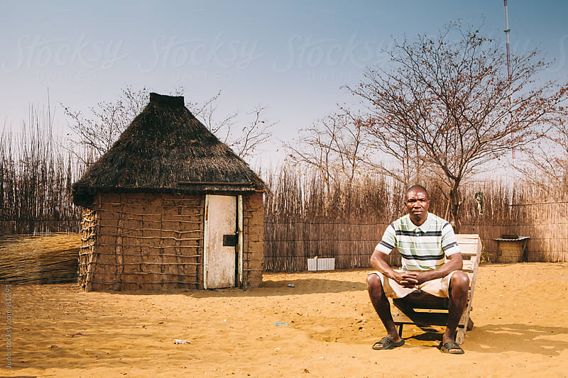 African Hambukushu Man in front of his hut by Micky Wiswedel for Stocksy United