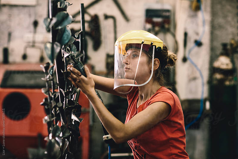 Young working woman using pneumatic file by Lior + Lone for Stocksy United