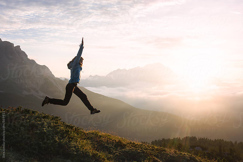 Hiker trail running and  jumping off the ground at sunrise by RG&B Images for Stocksy United