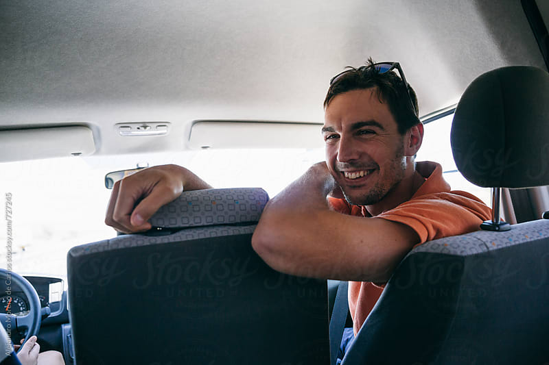 Young man laughing on the front of a van during a road trip by Alejandro Moreno de Carlos for Stocksy United