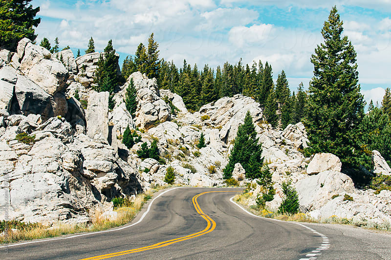 Mountain Road Winding Between White Boulders In Yellowstone National Park by Luke Mattson for Stocksy United