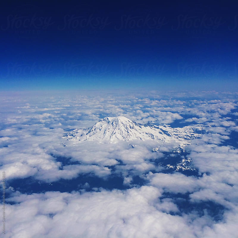 A mobile phone capture of Mount Rainier from an airplane.  by Kristen Curette Hines for Stocksy United