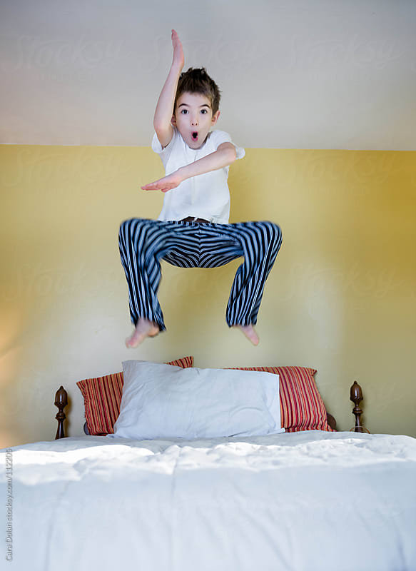 Silly boy jumps on his bed by Cara Dolan for Stocksy United