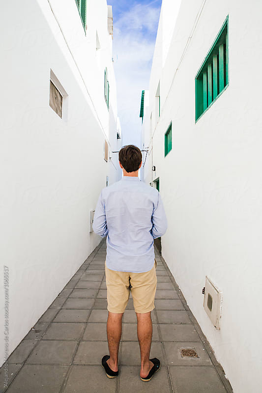 Back view of man standing in narrow street by Alejandro Moreno de Carlos for Stocksy United