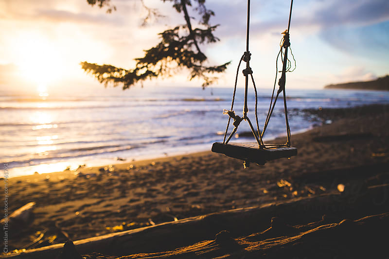 A tree swing hung overlooking the ocean at sunset by Christian Tisdale for Stocksy United
