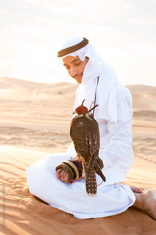 Arabian man in the desert with falcon. Dubai. U.A.E. by Hugh Sitton for Stocksy United