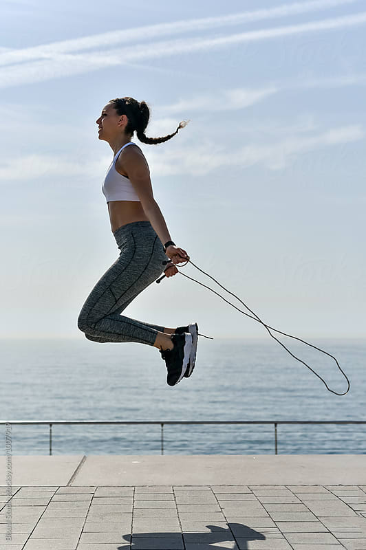 Fit woman working out in front of the sea by Bisual Studio for Stocksy United