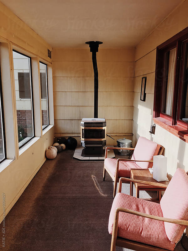 Sunny porch with two pink chairs and a woodstove by KATIE + JOE for Stocksy United