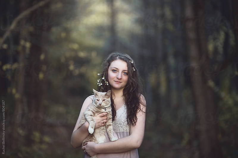 A young woman poses with her cat in the woods at sunset by Rachel Bellinsky for Stocksy United