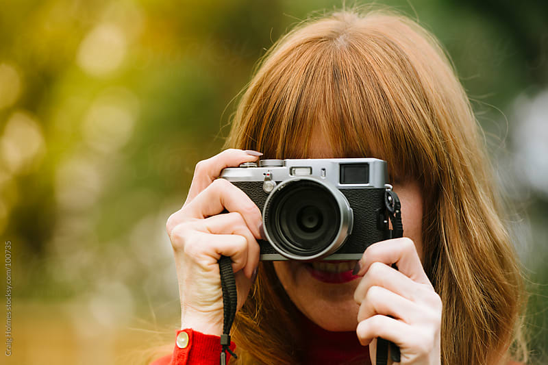Woman taking a photo with a camera by Craig Holmes for Stocksy United