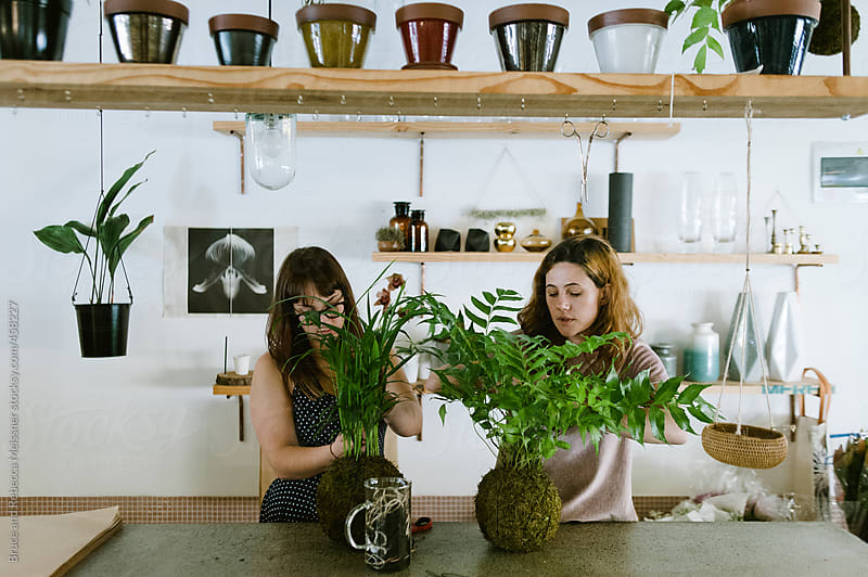 Two girls in a Flower Shop by Bruce and Rebecca Meissner for Stocksy United