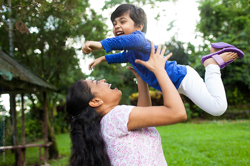 Mother throwing her daughter up in the air,happy family by Saptak Ganguly for Stocksy United