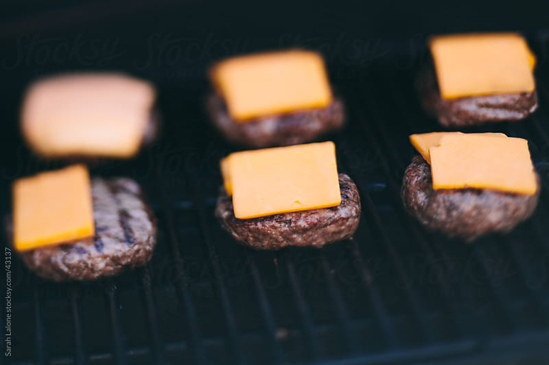 BBQ: Burgers on a grill with cheddar cheese. by Sarah Lalone for Stocksy United