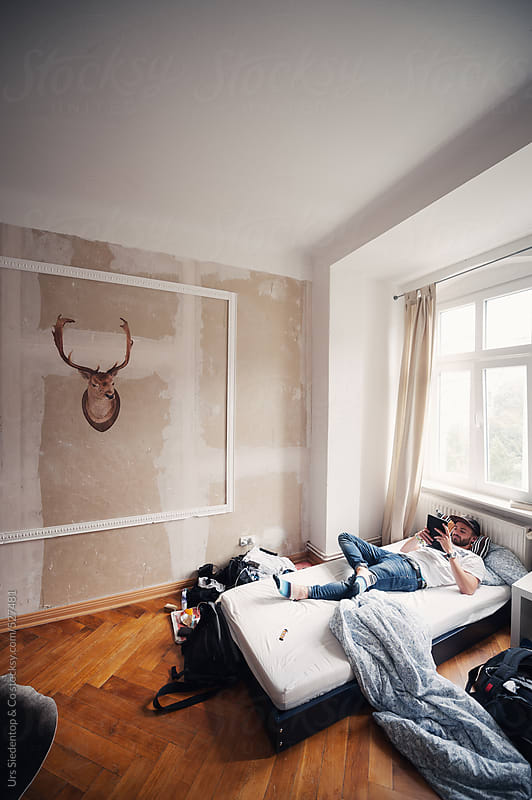 Man with tablet relaxing on bed by Urs Siedentop & Co for Stocksy United