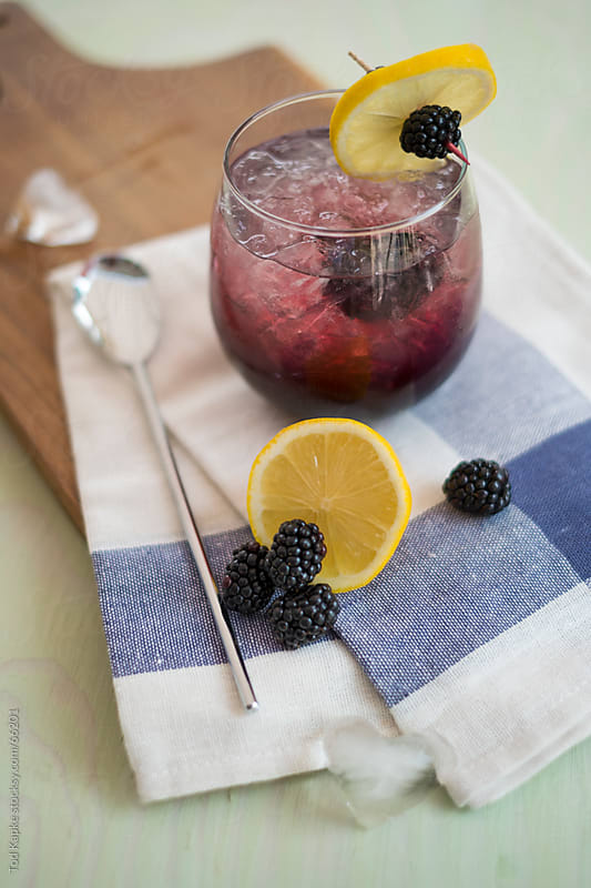 black berry cocktail on cutting board by Tod Kapke for Stocksy United
