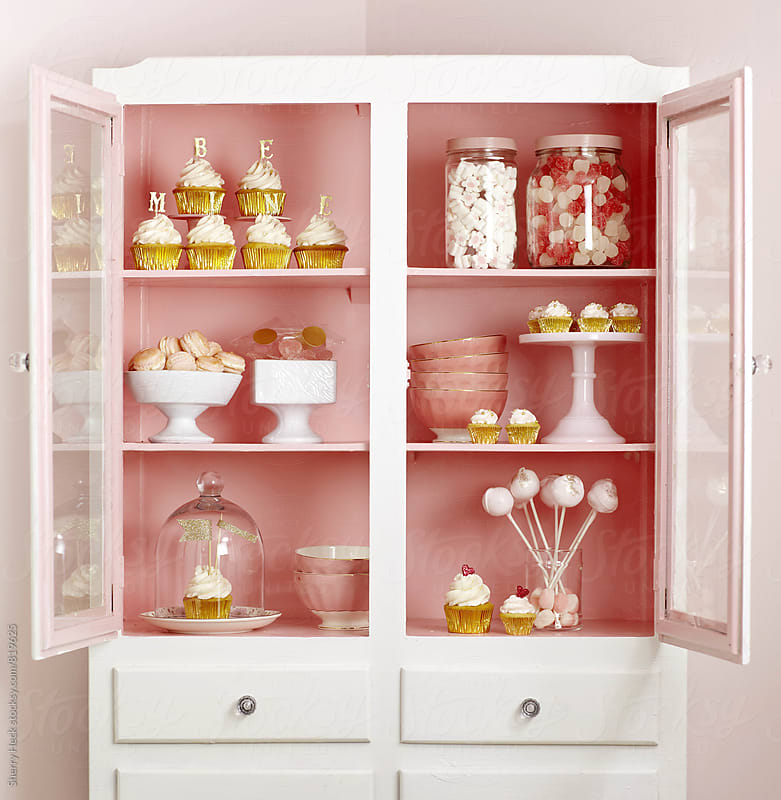 A collection of sweets displayed in a pink and white cabinet by Sherry Heck for Stocksy United