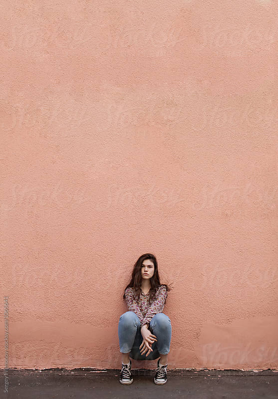 Teenager sitting on her haunches in a high wall by Sergey Filimonov for Stocksy United