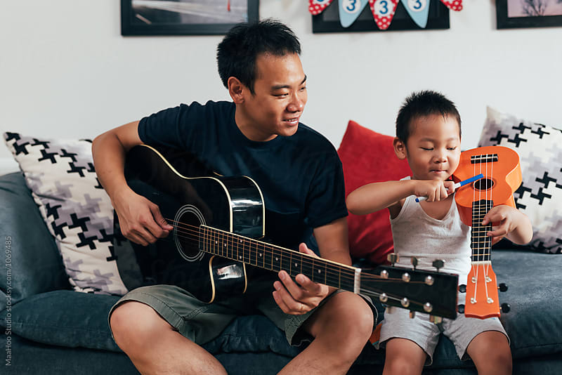 Father and son playing musical instruments by MaaHoo Studio for Stocksy United