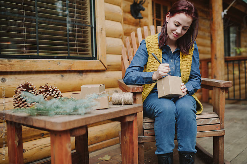 woman writing on gift box with smile in front of cabin by Kristin Rogers Photography for Stocksy United
